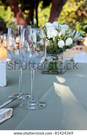 Wedding table setting with glasses of wine and white flowers - stock photo