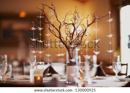 Wedding table setting with nature theme of bonsai tree and origami birds - stock photo