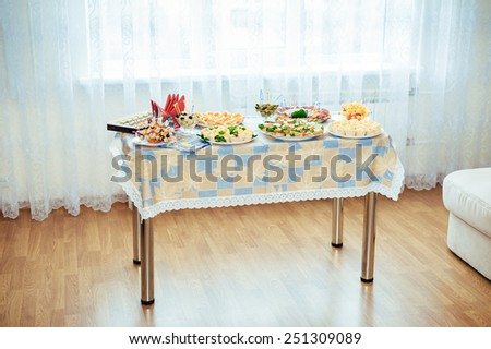 Wedding Table with food. Served for a banquet table. Wine glasses with napkins, glasses and salads. - stock photo