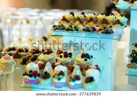 Wedding table with sweet fruit tasty desserts - stock photo