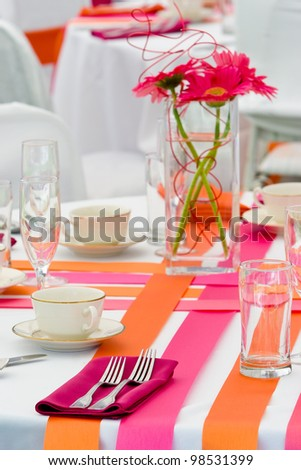 Wedding tables decorated in orange and pink for a funky wedding - stock photo
