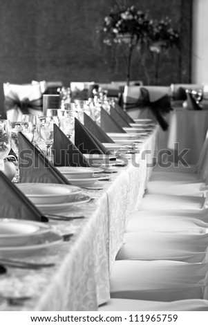 wedding tables set for fine dining or another catered event - black and white - stock photo