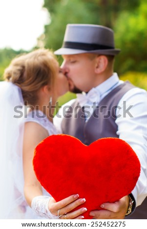 Wedding, the bride and groom with heart kiss - stock photo