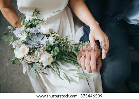 Wedding. The girl in a white dress and a guy in a suit sitting on a wooden chair, and are holding a beautiful bouquet of white, blue, pink flowers and greenery, decorated with silk ribbon - stock photo