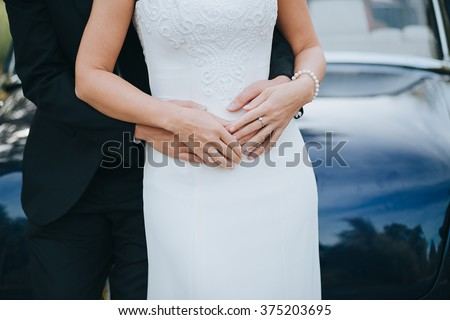 Wedding. The groom in a suit hugs bride in a white dress on a background of blue cars. In the hands of the bride's jewels - stock photo