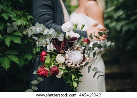 Wedding. The guy and the girl in a white dress standing and holding in his hands a bunch of red, white flowers and greenery