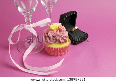 Wedding theme bridal pair of champagne flute glasses with pink cupcake and wedding ring in black jewelry box against a pink background. - stock photo