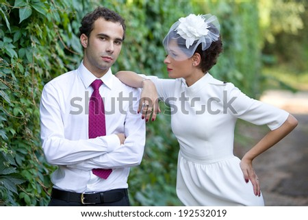 Wedding theme. Bride in stylish sheath dress with a hat with a veil looks at the groom. - stock photo