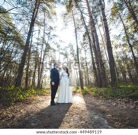 wedding theme, holding hands newlyweds . wedding couple, beautiful young bride and groom standing in a park - stock photo