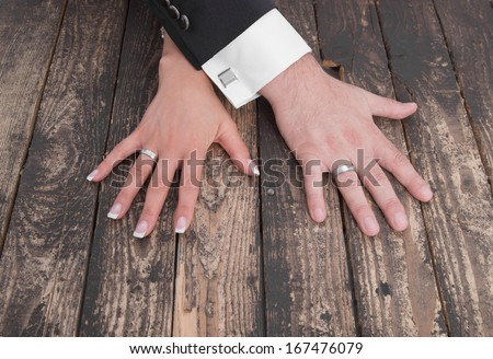 Wedding theme, man and woman hands on a wooden floor - marriage