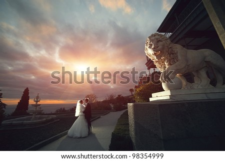 wedding theme, the bride and groom embracing at sunset near the statue lion - stock photo