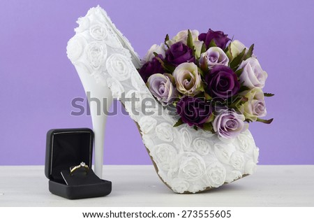 Wedding theme white floral bridal shoes with flowers on shabby chic white table and purple background.  - stock photo