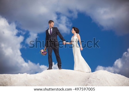 Wedding travel. Bride and groom are on the top of a mountain of white volcanic sand on a background of blue sky and white clouds. Honeymoon couple