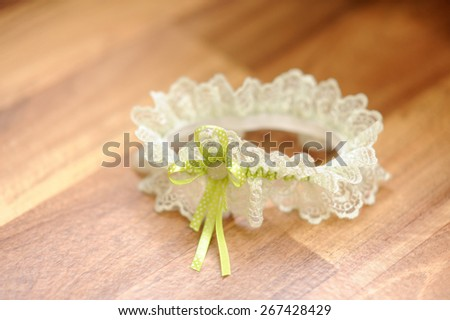 Wedding white garter lies on a floor and waiting on bride - stock photo