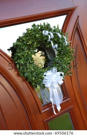 Wedding wreath with white bow decorating door - stock photo
