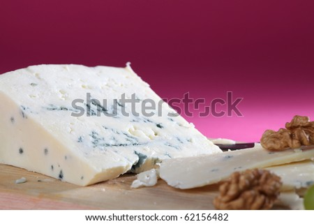 Wedge of blue cheese on cutting board with walnuts and grapes - stock photo