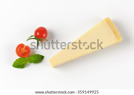 wedge of fresh parmesan cheese and cherry tomatoes on white background - stock photo