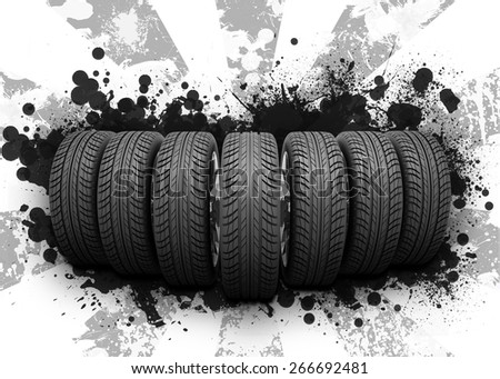 Wedge of new car wheels. Abstract background is black blotches and gray stripes at center