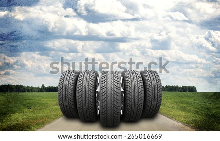 Wedge of new car wheels on road stretches into the distance. Roadsides and green grass field. Sky with clouds in background - stock photo