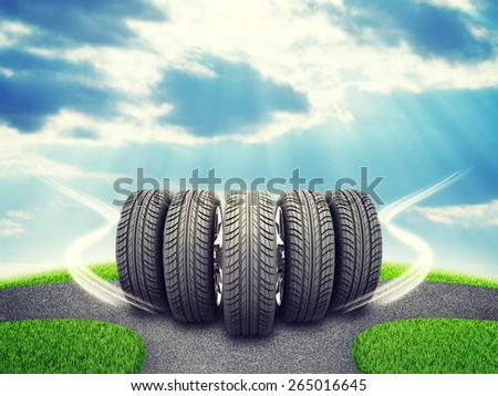 Wedge of new car wheels. Road fork  and green grass field. Sky with clouds and sun beams in background - stock photo