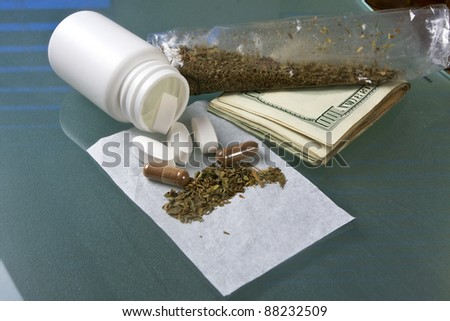 weed, money and pills on a glass table - stock photo