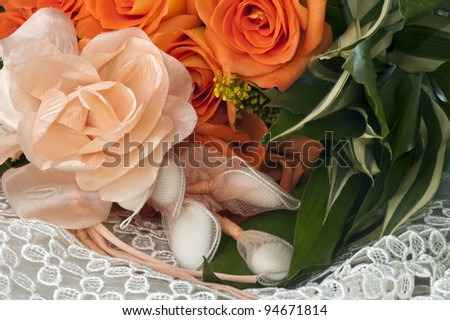weeding Favors and orange roses on white lace - stock photo