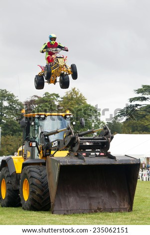 WEEDON, UK - AUGUST 28: One of the riders of the stunt duo, Kangaroo Kid, team jumps his ATV over a line of parked cars and an earth mover at the Bucks County show on August 28, 2014 in Weedon - stock photo