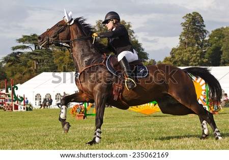 WEEDON, UK - AUGUST 28: The eventual winner of the show jumping accumulator competition lines her horse up to jump one of the fences at the Bucks County show on August 28, 2014 in Weedon.  - stock photo