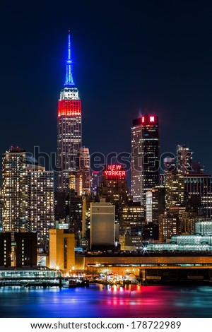 WEEHAWKEN, NJ, UNITED STATES - FEBRUARY 17, 2014: Empire State Building by night. The top of the iconic skyscraper displays the American flag colors, blue-white-red, in honor of Presidents' Day.