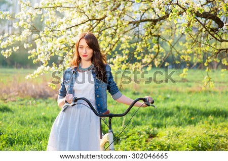 Week end in park. Attractive young brunette woman  walking with a bicycle against nature background. - stock photo