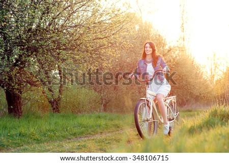 Week end in spring park. Attractive young brunette woman riding on bicycle against nature background. - stock photo
