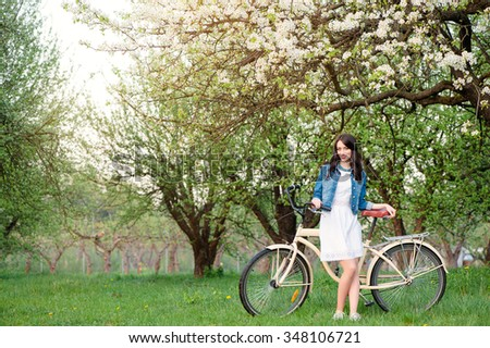 Week end in spring park. Attractive young brunette woman staying with a bicycle against nature background. - stock photo