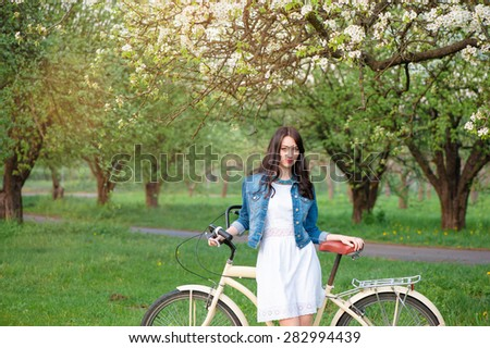 Week end in spring park. Attractive young brunette woman walking with a bicycle against nature background. - stock photo