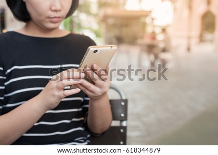 Weekend activity scene of adult Asian woman using mobile phone at coffee shop. Urban lifestyle with technology concept.