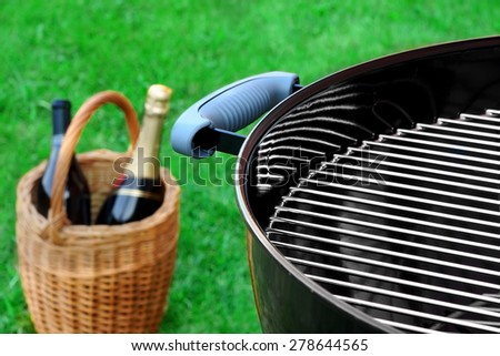 Weekend Barbecue Picnic Scene With Wine In Basket And Grill - stock photo