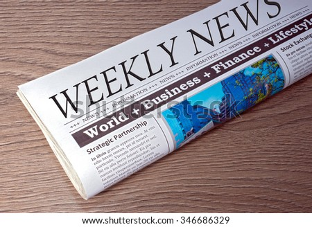 Weekly News - Newspaper on wooden background - stock photo