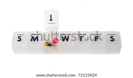 Weekly pill box with selection of medication - stock photo