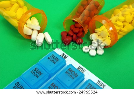 Weekly pill organizer with pills on green background
