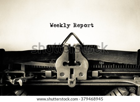 Weekly Report message typed on vintage typewriter  - stock photo