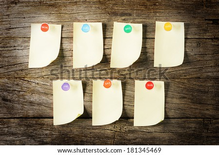 Weekly Sticky Note with colorful pin over wooden background - stock photo
