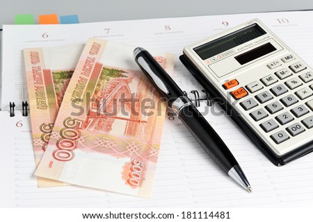 Weekly with black pen, calculator and money close up - stock photo