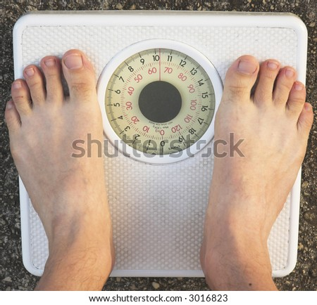 Weighing in on the bathroom scales. - stock photo