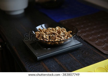 Weighing nuts on the digital scale - stock photo