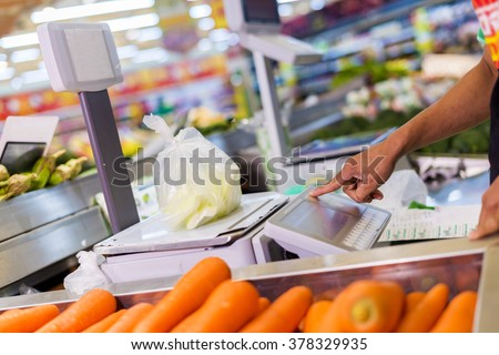 weighing of vegetable on electronic scales in supermarket.  - stock photo