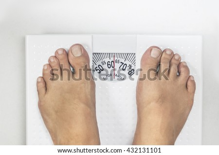 Weighing on analog weight Scale - stock photo