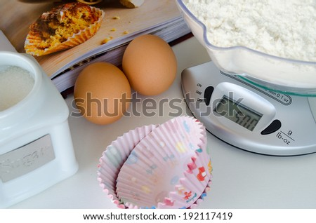 Weighing scale with baking ingredients (flour, sugar, eggs), cupcakes cup and a cooking book - stock photo