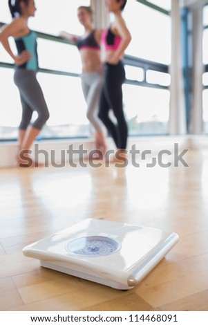 Weighing scales on floor of fitness studio - stock photo