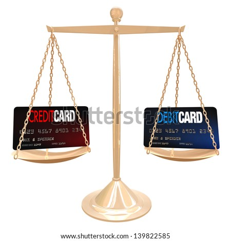 Weighing the differences between a credit and debit card - stock photo