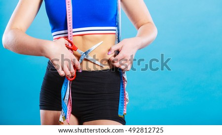 Weight gain diet liposuction concept. Woman with measure tapes pinches in the fat at the waist, holding scissors cut fold skin