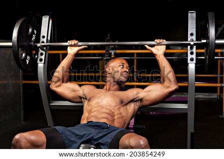 Weight lifter at the bench press about to lift a barbell. - stock photo